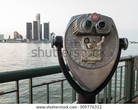 Detroit Sightseeing from Windsor. Sightseeing tourist binoculars overlooking downtown Detroit, Michigan on a summer afternoon from Windsor, Ontario, Canada. - stock photo