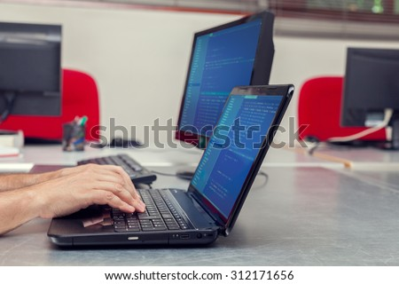 Developer working on source codes on laptop at office. - stock photo