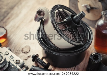 Developing tank with its film reels, photo film rolls, cassette, vintage camera and chemical reagents. - stock photo