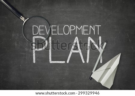 Development plan concept on black blackboard with empty paper sheet and coffee cup - stock photo