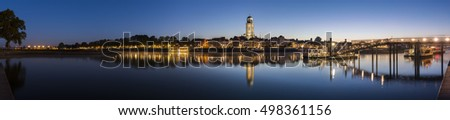 Deventer, The Netherlands - October 9, 2016: Panorama of Deventer at the IJssel in the morning during blue hour with the Great Church or Lebuineskerk in the province Overijssel, The Netherlands.
