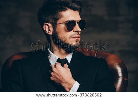 Devil is in details.Portrait of young handsome man in suit adjusting his tie and looking away while sitting in leather chair against dark grey background - stock photo