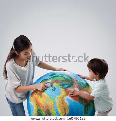 Devoted mother teaching her son about oceans and continents using a model of planet Earth.