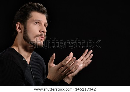 Devout man. Portrait of devout bearded man praying and holding his hands clasped - stock photo