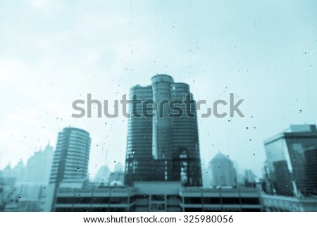 dew drops on a window glass after the rain view of buildings in the city