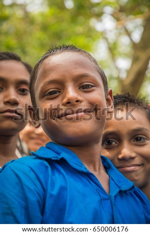 DHAKA, BANGLADESH - MAY 26, 2017: Three naughty looking school boys are looking in the camera in a village setting