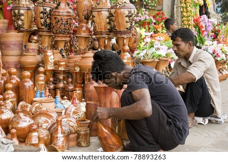 DHAKA, BANGLADESH – SEPTEMBER 21: Two unidentified men paint clay-made pottery in a roadside shop on September 21, 2010 in Dhaka, Bangladesh. Shops like this sell handcrafts to tourists and locals. - stock photo