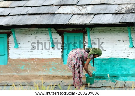 DHAMPUS, NEPAL - OCTOBER 8: Nepali woman paints her houses.s facade in green on October 8, 2012 in Dhampus-Annapurnas Tour trekking route-foothills of the Himalayas. Kaski district-Gandaki zone-Nepal. - stock photo