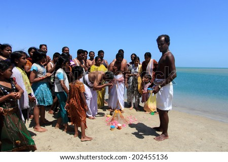 DHANUSHKODI, INDIA - OCT 06: Unidentified Hindu pilgrims do rituals at the sacred confluence on October 06, 2013 in Dhanushkodi, Tamil Nadu, India. Dhanushkodi is a Hindu pilgrimage site in India. - stock photo