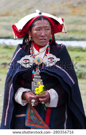 DHO TARAP, DOLPO, NEPAL - SEPTEMBER 11: Tibetan woman with offering flowers waiting for for a puja ceremony during Dho Tarap Full Moon Festival on September 11, 2011 in Dho Tarap village, Nepal/