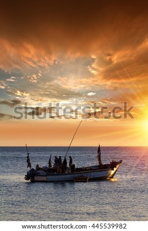 dhow fishing boat heading out to sea for a night of fishing against the ocean and warm yellow sky and sunlight.