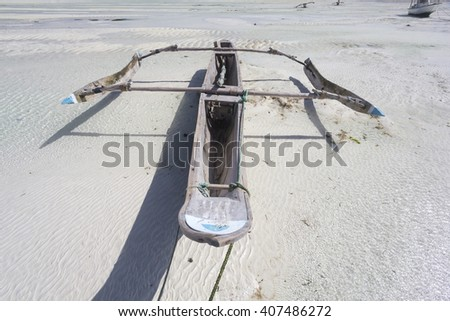 Dhow wooden boat lying dry at low tide on a beach at the Indian Ocean near Zanzibar, Tanzania - stock photo