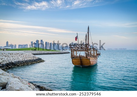 Dhows moored off Museum Park in central Doha, Qatar, Arabia, with some of the buildings from the city's commercial port in the background. - stock photo