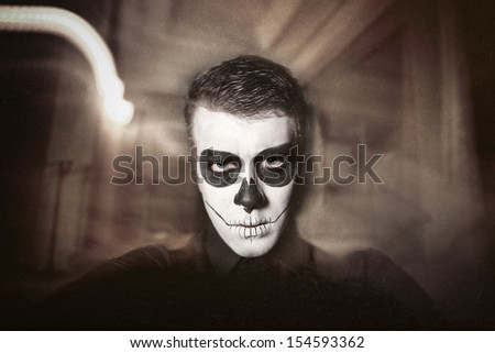 Dia de los Muerto Costume - Day of the dead is a mexican holiday. Here is a man with skull face and blurry background - stock photo