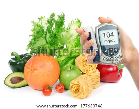Diabetes concept glucose level blood test meter in hand and healthy organic food fruits and vegetables on a white background - stock photo