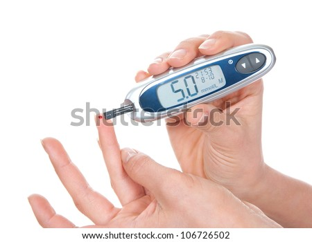 Diabetes measuring glucose level blood test using ultra mini glucometer and small drop of blood from finger and test strips isolated on a white background - stock photo