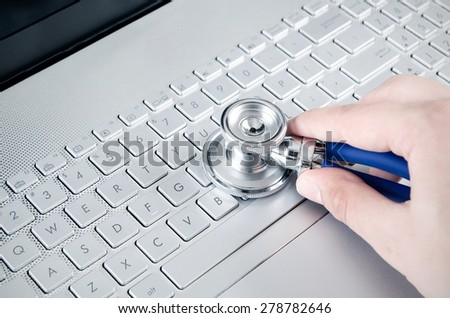 Diagnosis and repair of computers. Stethoscope on laptop - stock photo