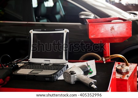 Diagnostic machine tools ready to be used with car in background - stock photo