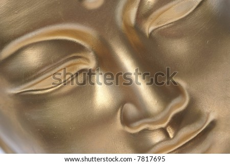 Diagonal close up of golden buddha face. - stock photo