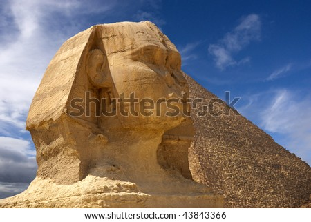 Diagonal front-on view of Sphinx with a pyramid in the background. Blue skies and clouds overhead - stock photo