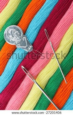 Diagonal group of bright colorful threads with needles - stock photo