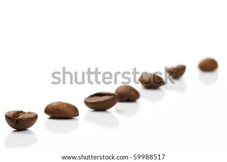 diagonal row of coffee beans on white background