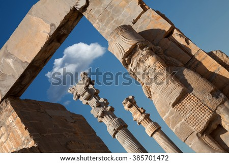Diagonal shot from Achaemenid Lamassu guarding the entrance Gate of All Nations in Persepolis of Shiraz against blue sky with single white cloud in the middle of gate. - stock photo