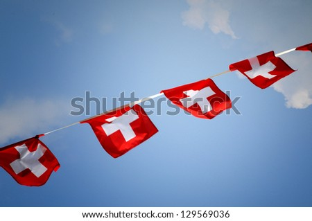 Diagonal streamer of bunting with the national flag of Switzerland flying for a festival celebration or patriotic event against blue sky - stock photo