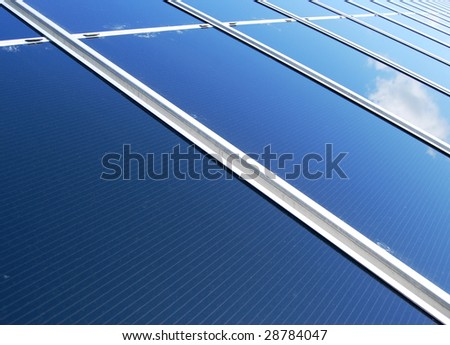 Diagonal view of a solar energy panel field with cloud reflection