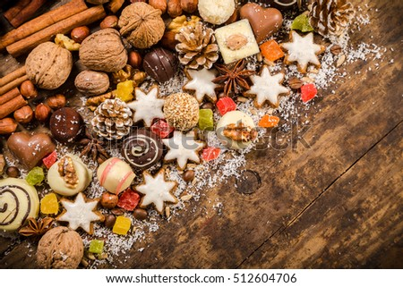 diagonal wooden background with candies, nuts, cookies, chocolate, dried fruits and other sweets, empty space for text