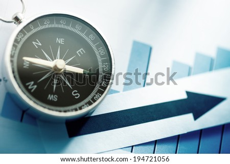 Diagram concept with compass and arrow in blue toning - stock photo
