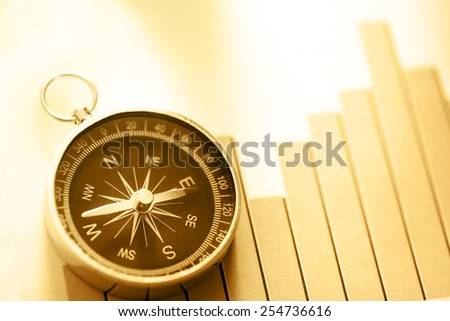 Diagram concept with compass and arrow in sepia toning - stock photo