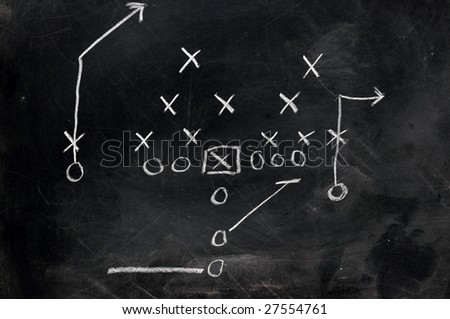 Diagram of football play on black chalkboard.