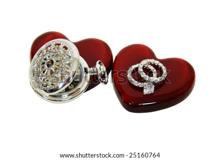 Diamond engagement ring with facets that sparkle brightly in the light symbolizing eternity of love, Red glass heart symbolizing love and romance, Silver pocket watch with a metal chain - stock photo
