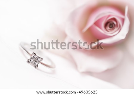 Diamond engagement ring with pink rose on background (shallow depth of field, bleached) - stock photo