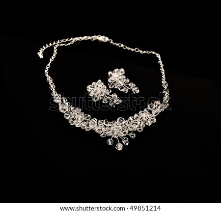 Diamond necklace and earrings on a black background - stock photo