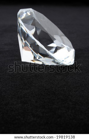 Diamond on black velvet with copy space - stock photo