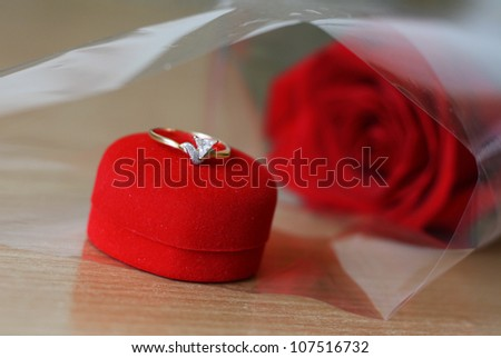 diamond ring on the red box and red roses in the background