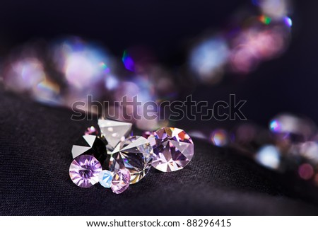 Diamond (small purple jewel) stones heap over black silk cloth background - stock photo
