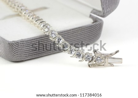 Diamond tennis bracelet in box isolated on white - stock photo