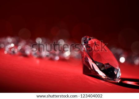 Diamonds on red background with focus on one in foreground - stock photo