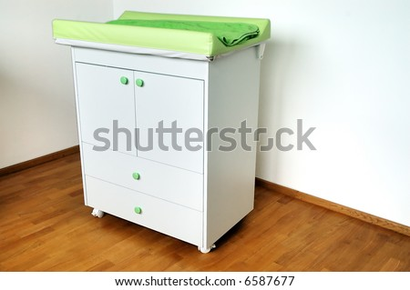 Diapers changing table on hardwood floor - stock photo