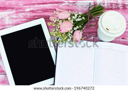 diary, a tablet computer, a glass of coffee and  lilies of valley and tulips on the table - stock photo