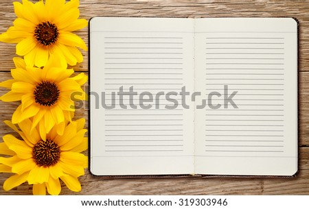 Diary and ornamental sunflowers on wooden background - stock photo