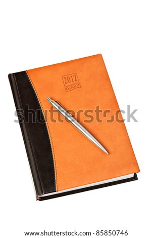 Diary for 2012 year  with leather cover and metal pen on table isolated on white background