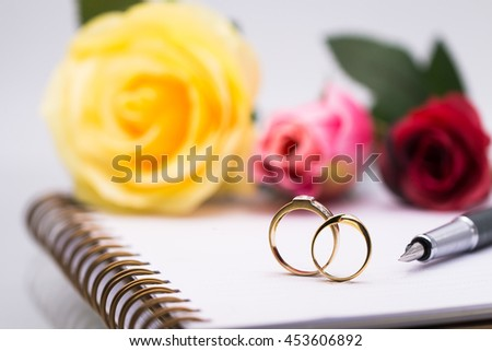 Diary note with couple wedding rings and quill pen (Organizer ,agenda, book, diary) - stock photo