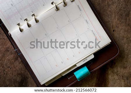 Diary on a wooden table - stock photo