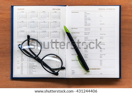 Diary planner book open year 2016 calendar page with glasses and pen on the wooden desk - stock photo