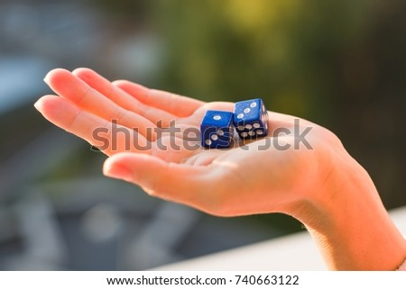 Dice 1 3 in the female hand, sunset background. Gambling devices. Game of chance concept.