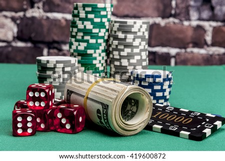 Dice, money and chips on green table - stock photo